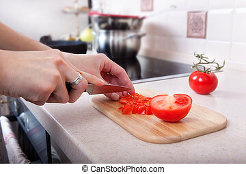 woman cuts tomatoes with a knife on the kitchen table.