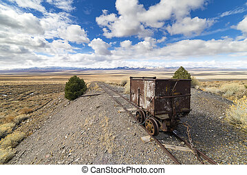 Old mining ore cart on tracks underneath a beautiful blue...