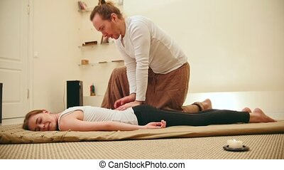Young woman gets enjoyment during thai massage treatment,...