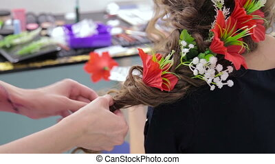 4 shots. Hairstylist, hairdresser finishing creative hairstyle with flowers for teen girl in white make up room