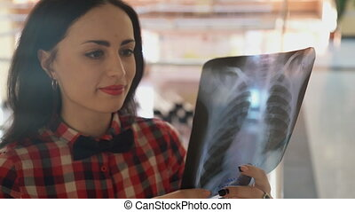 Woman with a butterfly looking at x-ray picture of the thorax.