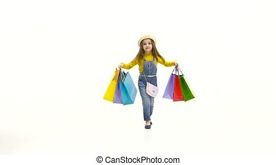 Little girl with multi colored packages is indoors. White background. Slow motion