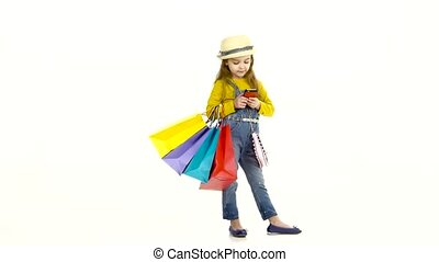 Little girl holding bags and wrote messages on the phone,...