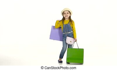 Little girl shows off its fashionable shopping. White background. Slow motion