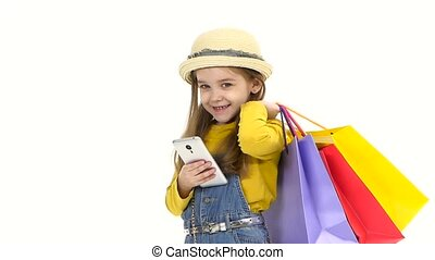 Shopping Little girl holding a mobile phone bags and looking...
