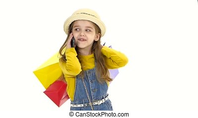 Little girl holding bags and talking on the phone, smiling....