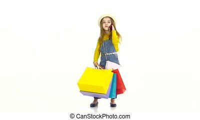 Little girl holding bags and talking on the phone, smiling. White background