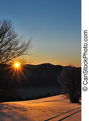 Rising Sun - Winter scenery of the sun rising behind the...