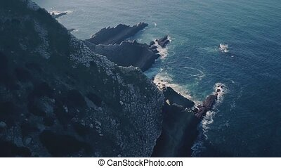 Flight Above Sharp Cliff in Ocean, aerial view