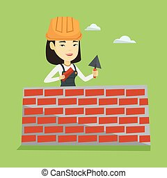 Bricklayer working with spatula and brick. - Asian female...