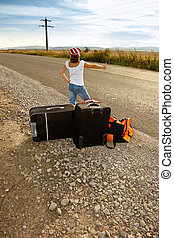 Young hitch-hiker girl standing on road side afternoon with...