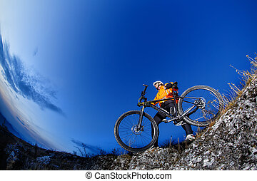 Cyclist Riding the Bike Down Hill on the Mountain Rocky Trail at Sunset. Extreme Sports