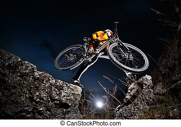 Cyclist Riding the Bike Down Hill on the Mountain Rocky...