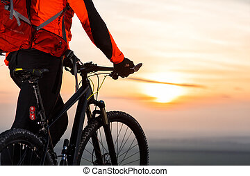 cyclist on mountain-bike at sunset, cyclist on the background of beautiful sunset.