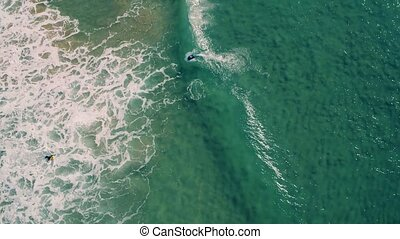 Aerial View of Surfers Riding Green Ocean Waves