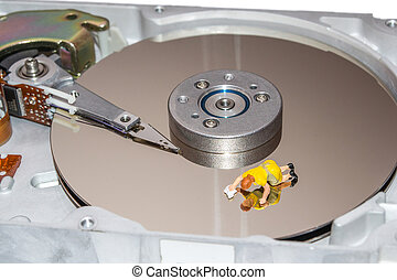Cleaning the hard disk. A woman cleans a HDD. Figurine of a...