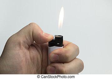 Hand holding a lighter. - Hand holding a lighter on a white...