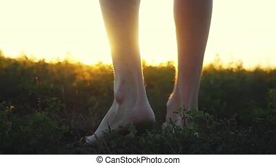 Close up of masculine feet go barefoot to the soft grass...