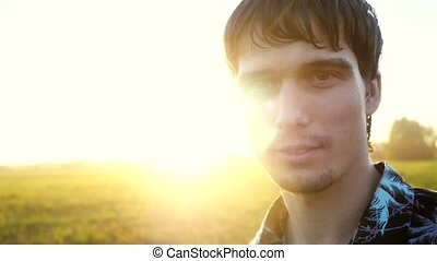 Portrait of smiles man looking at the sun during beautiful sunset with lense flare effects.