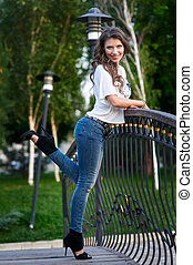 happy young woman in shirt and jeans standing on the bridge
