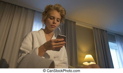 The girl after a shower sitting in bathrobe with phone -...