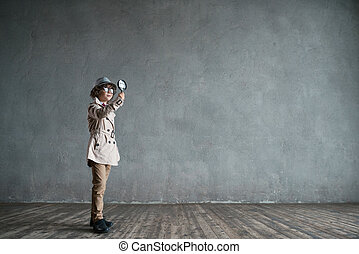 Detective - Little boy with a magnifying glass in studio