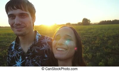 Happy young couple hugging on summer field and smiling, make...