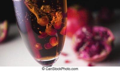 Garnet grains fall into champagne slow mo - Garnet grains...