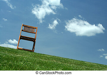 Wooden chair on a hilltop - A Wooden chair with grass and...