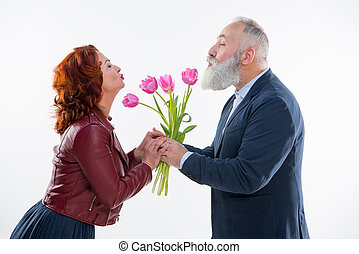 Man presenting flowers to woman - Side view of beautiful...