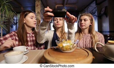 Female friends taking food picture with smartphone - Happy...
