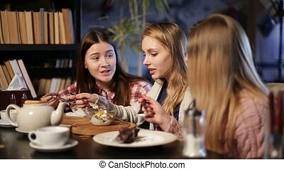 Two young teenage girls eating desserts in cafe - Pretty...
