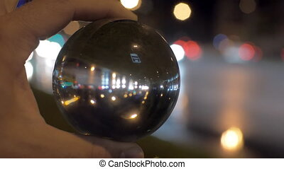 Looking at night city through glass ball - Close-up shot of...