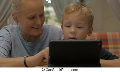 Child and mom with digital tablet in cafe - Mother and son...
