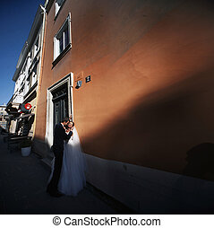 The couple in love embracing near wall