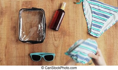 hands packing beach accessories to bag - summer holidays,...