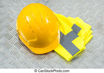 Hard Hat and Folded Safety Vest on Steel Checker Plate -...