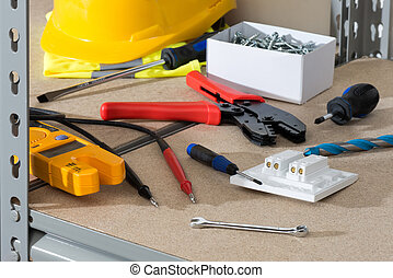 Electrician's Tools and Supplies on Cork-Covered Shelving -...