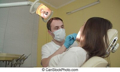 The dentist examines a female patient in the dental office.