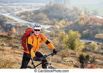 Man in helmet and glasses, with backpack stay on the bicycle under landscape with rocks and hill.
