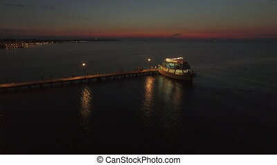 Aerial view of pontoon on the sea and people walking on it from cruise boat at the evening, Greece
