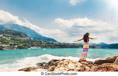 Relaxed woman with open arms from behind on sea. Girl from...