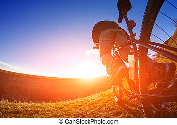 low angle view of cyclist standing with mountain bike on...