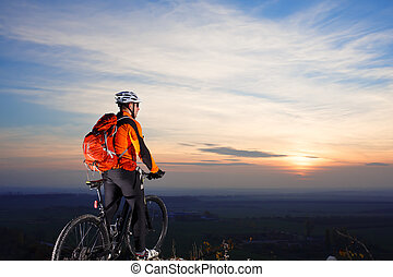 Sun rises behind man getting ready to ride his road bike on...
