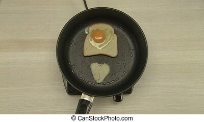 Cooking of breakfast with fried egg and toast - Man...