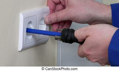 hands install electrical wall sockets - hands installing...