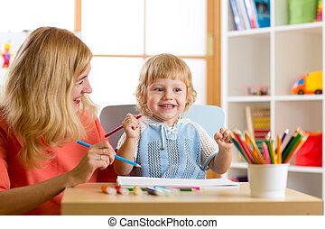 Mother playing with her kid son, drawing together