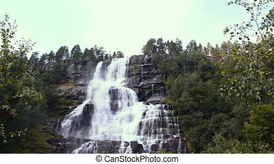 Waterfall Tvindefossen in sunny summer day, Norway - Three...