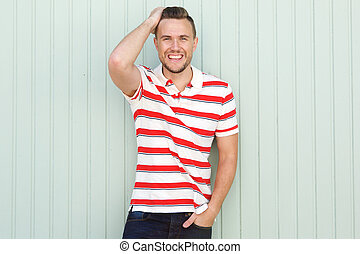 smiling young man standing against green wall with striped...