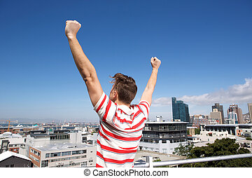 behind of young man with arms raised outsice